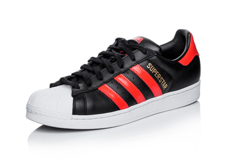LONDON, UK - JUNE 05, 2019: Adidas Originals Superstar black shoe with red stripes on white background. Zdjęcie Seryjne - 124998869