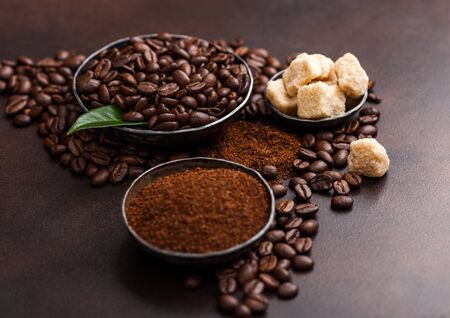 Fresh raw organic coffee beans with ground powder and cane sugar cubes with coffee trea leaf on brown. Stockfoto