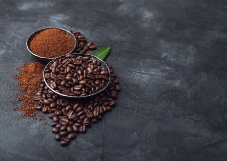 Fresh raw organic coffee beans with ground powder and coffee trea leaf on black. Space for text 版權商用圖片