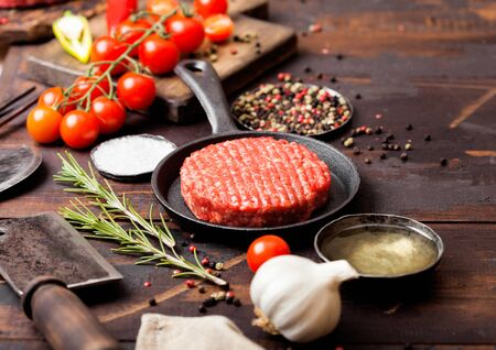 Fresh raw minced homemade farmers grill beef burger in frying pan with spices and herbs and meat hatchet on wooden board.