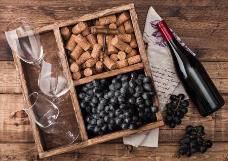 Bottle of red wine on wood with empty glasses with dark grapes with corks and opener inside vintage wooden box on grunge wooden background with linen towel.