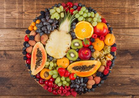 Fresh raw organic summer berries and exotic fruits in round large tray on wooden kitchen background. Papaya, grapes, nectarine, orange, raspberry, kiwi, strawberry, lychees, cherry.Top view