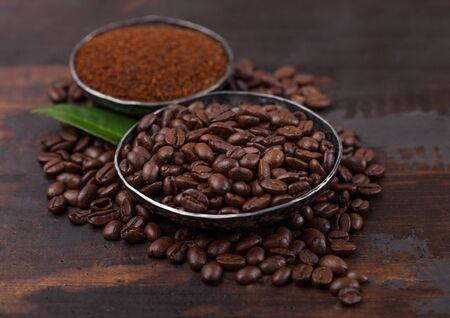 Fresh raw organic coffee beans with ground powder and coffee tree leaf on wood.