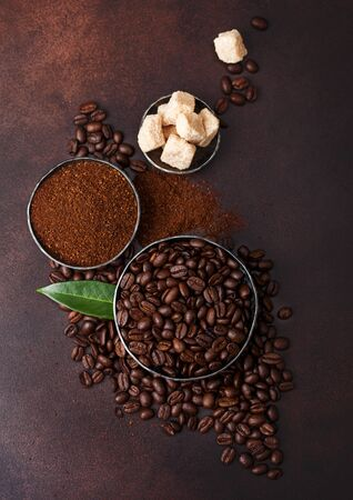 Fresh raw organic coffee beans with ground powder and cane sugar cubes with coffee trea leaf on brown.