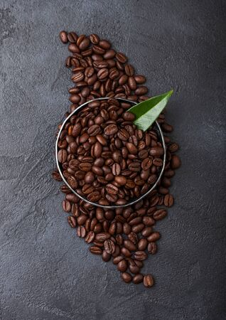 Fresh raw organic coffee beans in steel bowl with coffee trea leaf on black.