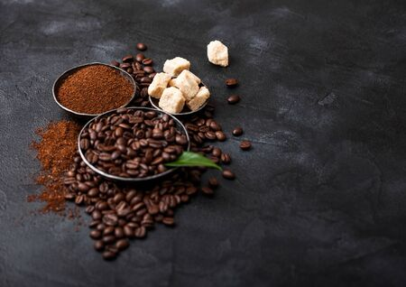 Fresh raw organic coffee beans with ground powder and cane sugar cubes with coffee trea leaf on black. Space for text.