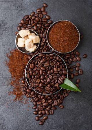 Fresh raw organic coffee beans with ground powder and cane sugar cubes with coffee trea leaf on black. Stok Fotoğraf