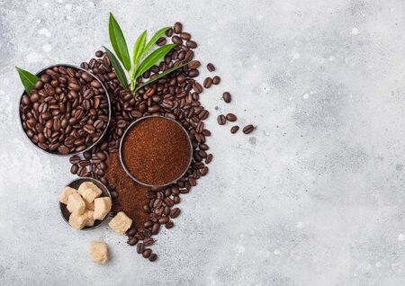 Fresh raw organic coffee beans with ground powder and cane sugar cubes with coffee trea leaf on light kitchen table. Space for text