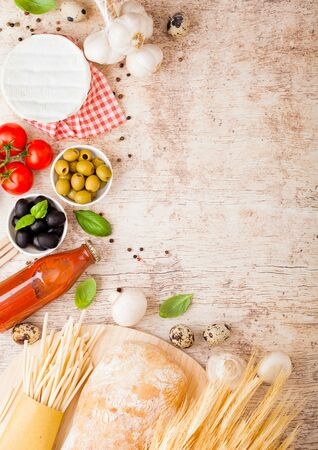 Homemade spaghetti pasta with quail eggs with bottle of tomato sauce and cheese on wood background. Classic italian village food. Garlic, champignons, black and green olives, oil and bread. Stok Fotoğraf