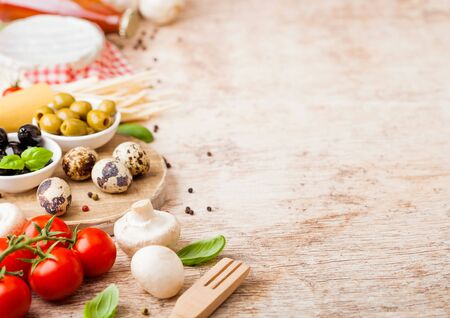 Homemade spaghetti pasta with quail eggs with bottle of tomato sauce and cheese on wood background. Classic italian village food. Garlic, champignons, black and green olives, oil and spatula Stok Fotoğraf