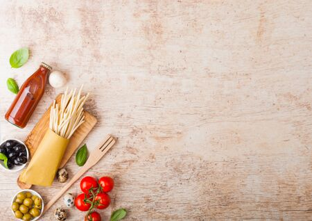 Homemade spaghetti pasta with quail eggs with bottle of tomato sauce on wood background. Classic italian village food. Garlic, champignons, black and green olives. Stok Fotoğraf