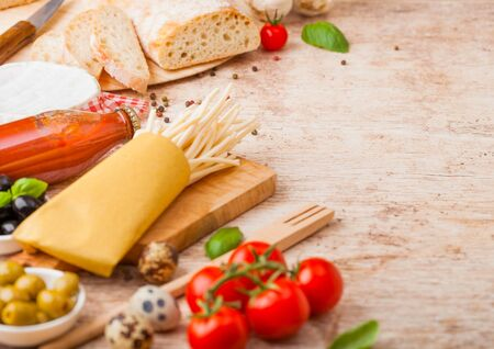 Homemade spaghetti pasta with quail eggs with bottle of tomato sauce and cheese on wood background. Classic italian village food. Garlic, champignons, black and green olives, bread and spatula. Stok Fotoğraf