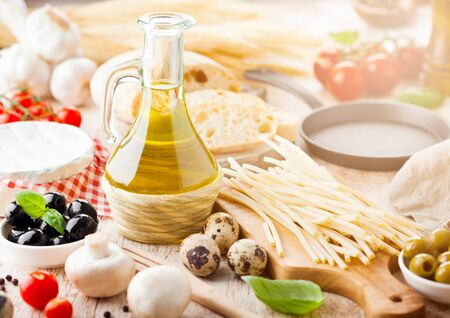 Homemade spaghetti pasta with quail eggs with botle of olive oil and cheese on wooden background. Classic italian village food. Garlic, black and green olives, oil and bread. Banque d'images
