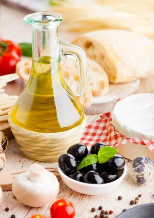 Homemade spaghetti pasta with quail eggs with botle of olive oil and cheese on wooden background. Classic italian village food. Garlic, black and green olives, oil and bread. Stok Fotoğraf