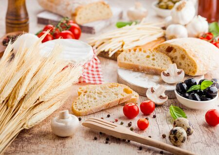 Homemade wheat bread with quail eggs and raw wheat and fresh tomatoes on wood background. Classic italian village food. Garlic, black and green olives. Wooden spatula