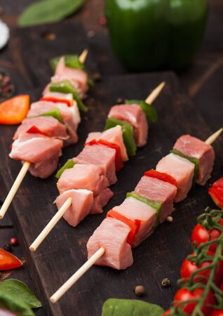 Raw pork and chicken kebab with paprika on chopping board with salt and pepper on wood. Zdjęcie Seryjne