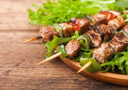 Grilled pork and chicken kebab with paprika in round wooden plate of lettuce salad on wood.