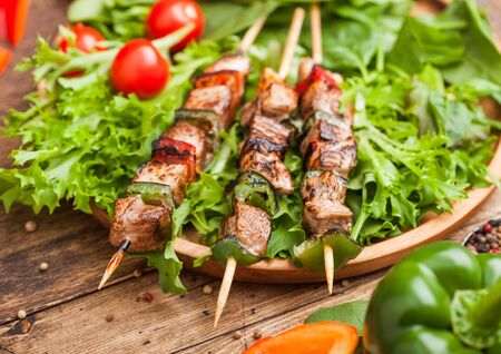Grilled pork and chicken kebab with paprika in round wooden plate of lettuce salad, on wooden background with tomatoes and spinach. Zdjęcie Seryjne