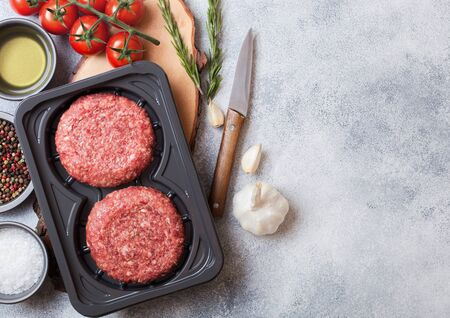 Plastic tray with raw minced homemade grill beef burgers with spices and herbs. Top view.