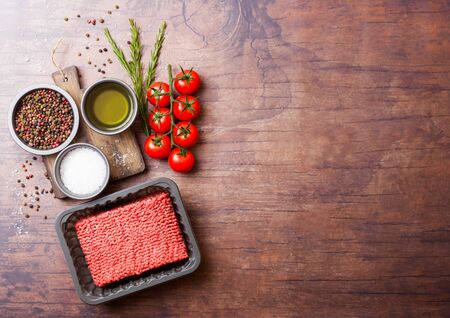 Tray with raw minced homemade beef meat with spices and herbs. Top view and space for text. On kitchen table background.