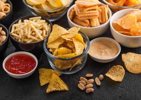 All classic potato snacks with peanuts, popcorn and onion rings and salted pretzels in bowl plates on black table. Twirls with sticks and potato chips and crisps with nachos and cheese balls. Zdjęcie Seryjne