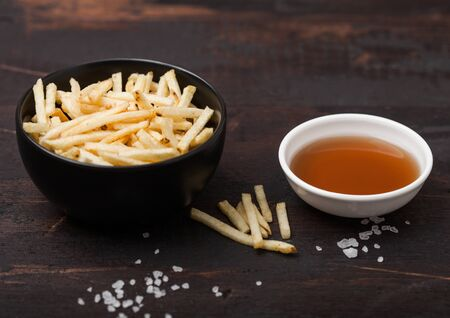 Salt and vinegar potato sticks in white bowl, classic snack with ketchup on wood.