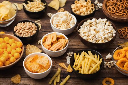 All classic potato snacks with peanuts, popcorn and onion rings and salted pretzels in bowl plates on wood. Twirls with sticks and potato chips and crisps with nachos and cheese balls. Top view Zdjęcie Seryjne