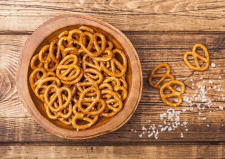Hard salted pretzels classic snack for beer in wooden bowl on wood. Top view
