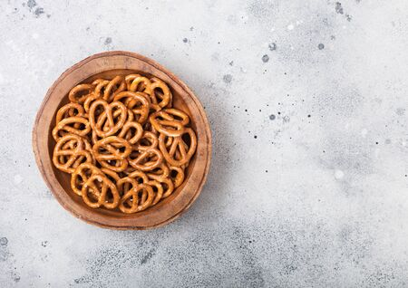 Hard salted pretzels classic snack for beer in wooden bowl on light table. Top view