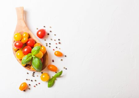 Organic Mini Tomatoes with basil and pepper in oilve wood plate on white background.