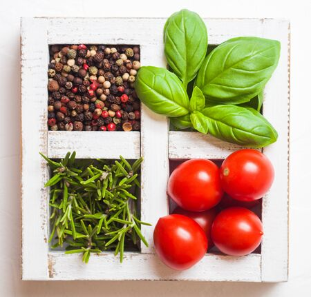 Organic Cherry Tomatoes with basil and pepper and rosemary in white wooden box on stone background.