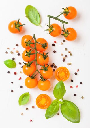Organic Cherry Orange Rapture Tomatoes on the Vine with basil and pepper on white kitchen stone background