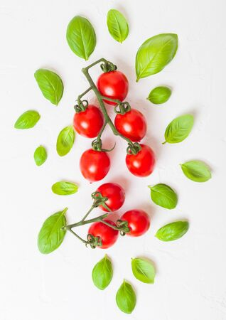 Organic Cherry Sugardrop Tomatoes on the Vine with basil and pepper on white kitchen stone background