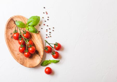 Organic Cherry Sugardrop Tomatoes on the Vine with basil and pepper in oilve wood plate on white background.