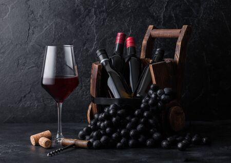 Elegant glass of red wine with dark grapes and mini bottles of wine inside vintage wooden barrel on black stone background. Zdjęcie Seryjne