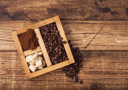 Vintage box of fresh raw organic coffee with beans and ground powder with cane sugar on wooden background.