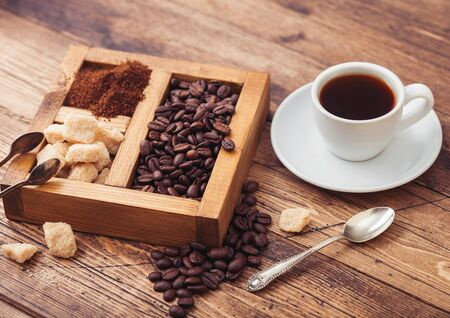 White cup of fresh raw organic coffee with beans and ground powder with cane sugar in vintage box on wooden background.