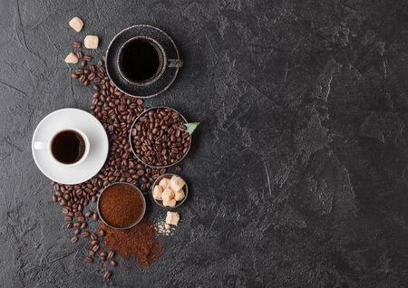 Black and white cups of fresh raw organic coffee with beans and ground powder with cane sugar cubes with coffee tree leaf on black background. Space for text