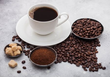 White cup of fresh raw organic coffee with beans and ground powder with cane sugar cubes with coffee tree leaf on light background. Top view