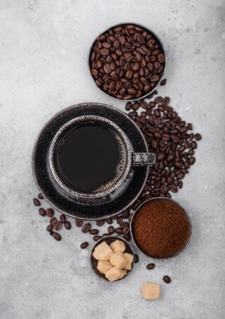 Cup of fresh raw organic coffee with beans and ground powder with cane sugar cubes with coffee tree leaf on light background. Zdjęcie Seryjne
