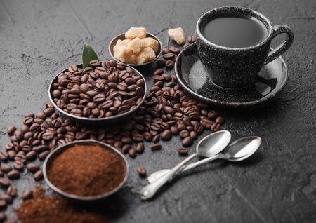 Kopje verse rauwe biologische koffie met bonen en gemalen poeder met rietsuikerklontjes met koffieboomblad op donkere achtergrond.