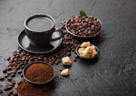 Cup of fresh raw organic coffee with beans and ground powder with cane sugar cubes with coffee tree leaf on dark background. Black ceramic mug.