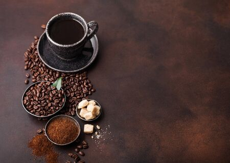 Cup of fresh raw organic coffee with beans and ground powder with cane sugar cubes with coffee tree leaf on dark background. Black ceramic mug Zdjęcie Seryjne