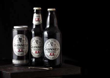 LONDON, UK - APRIL 27, 2018: Aluminium can and bottles of Guinness extra stout beer  on dark wooden background. Guinness beer has been produced since 1759 in Dublin, Ireland.