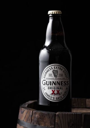 LONDON, UK - APRIL 27, 2018: Bottle of Guinness original stout beer on top of old wooden barrel. Guinness beer has been produced since 1759 in Dublin, Ireland. Sajtókép