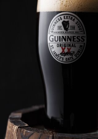 LONDON, UK - APRIL 27, 2018: Original glass of Guinness original stout beer on top of old wooden barrel. Guinness beer has been produced since 1759 in Dublin, Ireland.