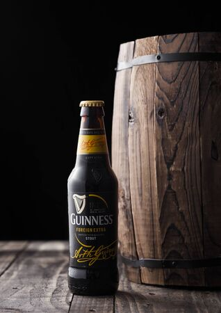 LONDON, UK - APRIL 27, 2018: Bottle of Guinness draught stout beer  next to old wooden barrel. Guinness beer has been produced since 1759 in Dublin, Ireland. Sajtókép