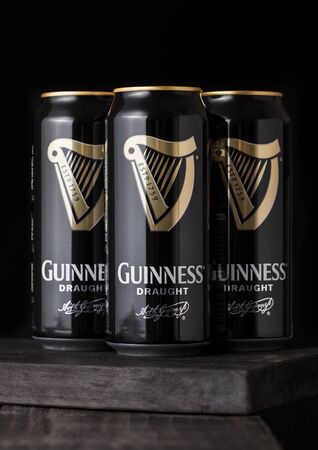 LONDON, UK - APRIL 27, 2018: Aluminium cans of Guinness draught stout beer bottle on dark wooden background. Guinness beer has been produced since 1759 in Dublin, Ireland.