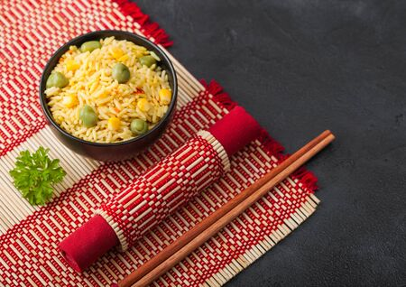 Black bowl with boiled organic basmati vegetable rice with wooden chopsticks on red bamboo placemat. Yellow corn and green peas with paprika.