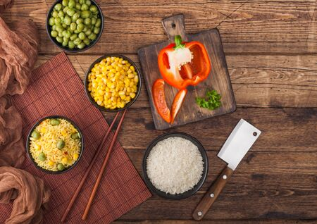 Black bowl with boiled organic basmati vegetable rice with wooden chopsticks on brown placemat with linen towel. Yellow corn and green peas with paprika slices and bowl of raw rice. Top view